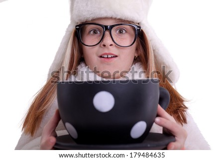 girl with glasses and a white winter hat, holding in his hand a large cup