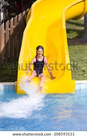 Girl with glasses for swimming sliding on toboggan at aqua park - stock photo