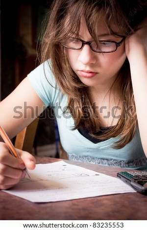 Girl with glasses frustrated with schoolwork - stock photo