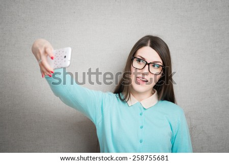 girl with glasses pictures of themselves on a mobile phone - stock photo