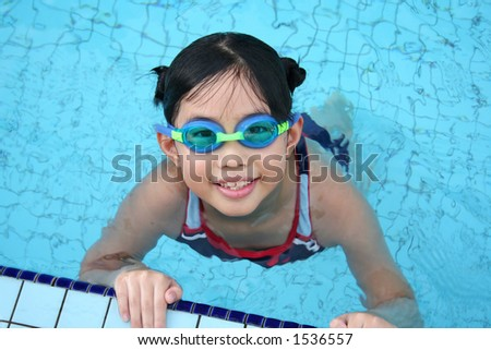 Girl with goggles in the swimming pool - stock photo