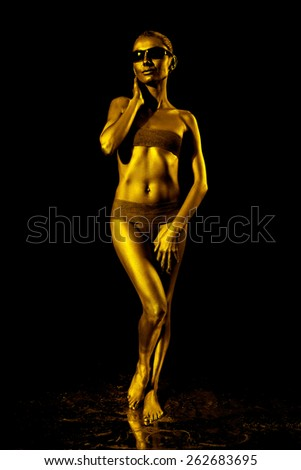 Girl with golden skin in sunglasses. Low key. - stock photo