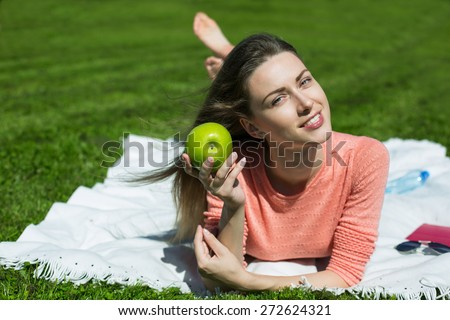 girl with green apple in hands lying on the grass - stock photo