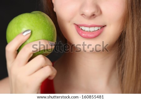 Girl with green apple on black background - stock photo