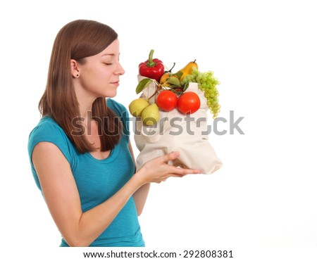 Girl with groceries. In her bag she has tomatoes, pears, lettuce, peppers, grapes and other healthy things.
