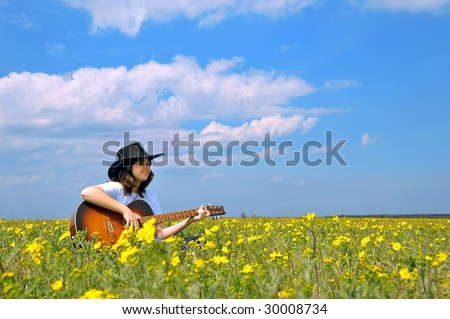 girl with guitar in a field - stock photo