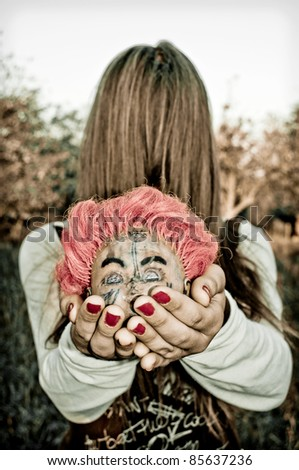 Girl with hair over face holding a severed head doll - stock photo