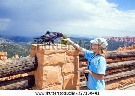 Girl with hand feeding crow on background  Bryce Canyon National Park, Utah, USA - stock photo
