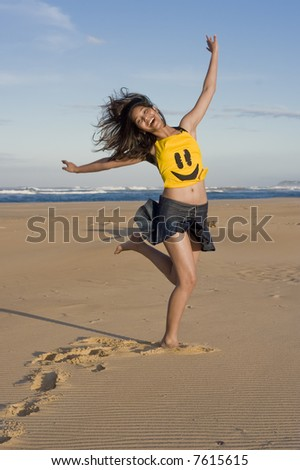 "Girl with ""happy Face"" top running at the beach - stock photo"