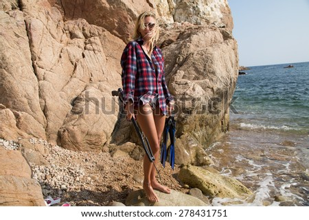 Girl with harpoon in flannel shirt on the rocky beach. - stock photo