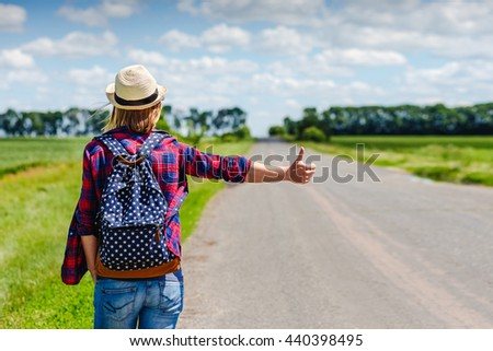 Girl with hat and backpack hitchhiking on the road - stock photo