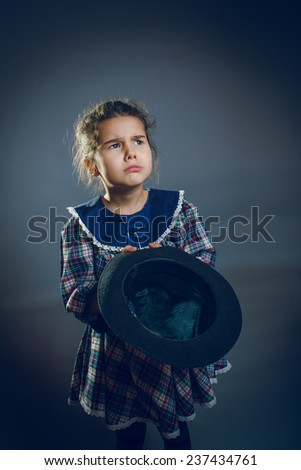 girl with hat in hand asking coins cross process - stock photo