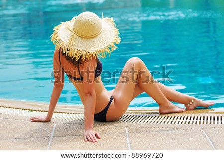 Girl with hat in tropical swimming pool - stock photo