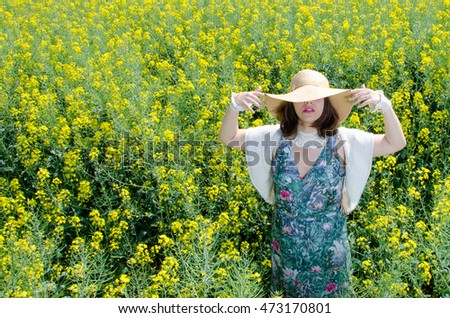 Girl with hat posing on a yellow field