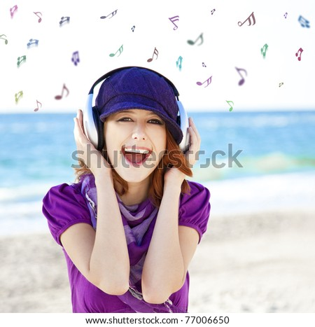 Girl with headphone and notes at the beach. - stock photo