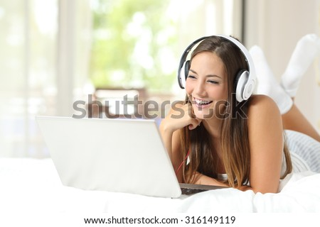 Girl with headphones listening to the music in a laptop on the bed at home - stock photo