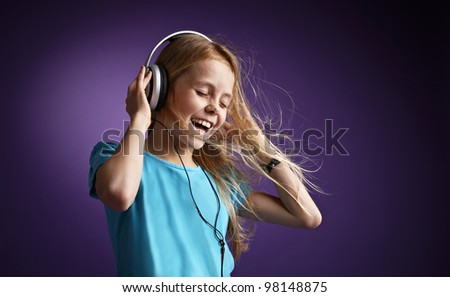 Girl with headphones on purple background - stock photo