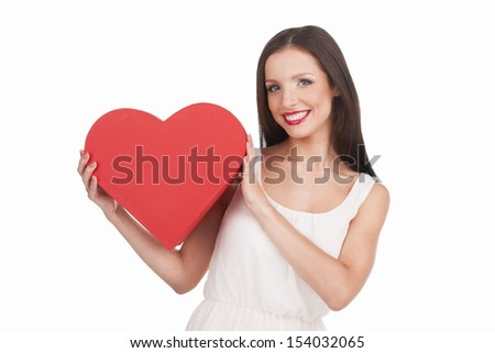 Girl with heart. Beautiful young woman holding paper heart and smiling while isolated on white