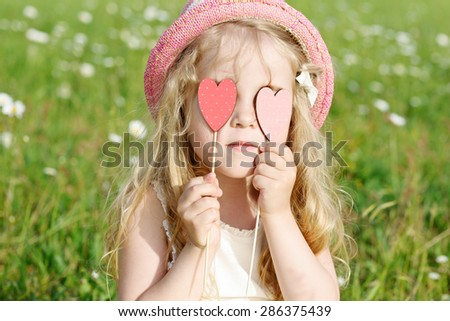 girl with hearts near the eyes in field - stock photo