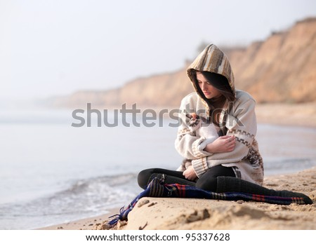 Girl with her cat at seashore in the cold day