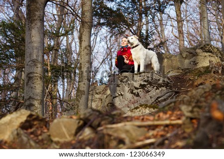 Girl with her dog in forest - stock photo