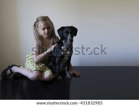 girl with her dog sitting on a shiny black floor against a white wall - stock photo