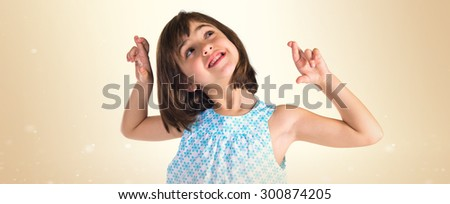 Girl with her fingers crossing over ocher background - stock photo