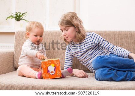 Girl with her little sister sit at a sofa and playing educational games