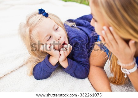 Girl with her mom on a picnic in park. Little blonde daughter fooling and showing funny face expressions and grimaces. Both lying on a plead on grass in blue dresses. Girl wearing blue bow in hair - stock photo