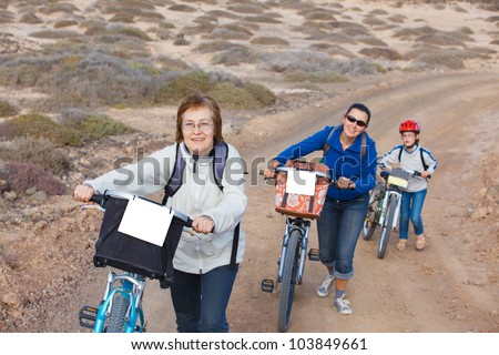 Girl with her mother and grandmother having a weekend excursion on their bikes on a summer day in beautiful landscape - stock photo