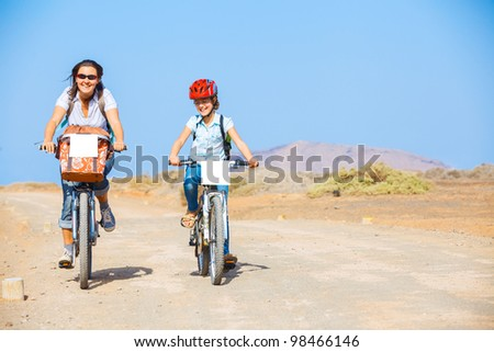 Girl with her mother having a weekend excursion on their bikes on a summer day in beautiful landscape - stock photo
