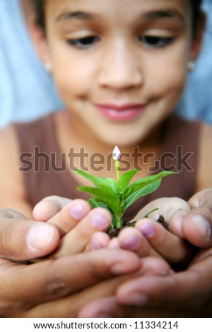 Girl with her mother holding a new flower - stock photo