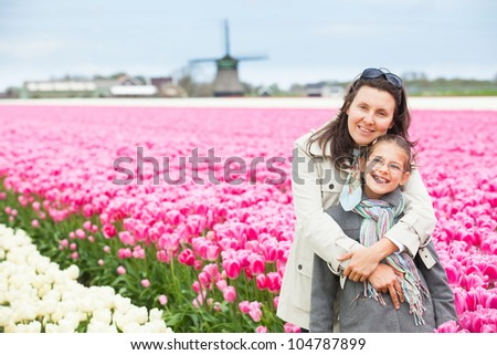Girl with her mother walks between of the purple tulips field - stock photo