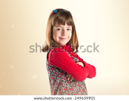 Girl with hers arms crossed over ocher background