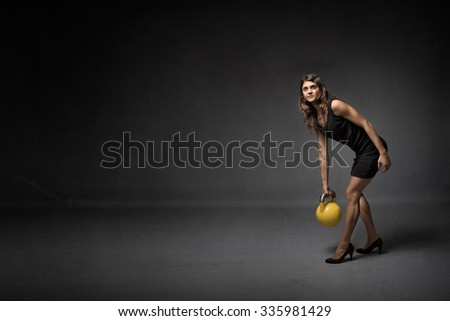 girl with kettlebell and high heels, dark background - stock photo