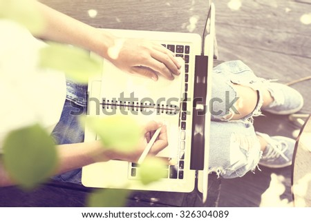 Girl with laptop and blank diary outdoors - stock photo