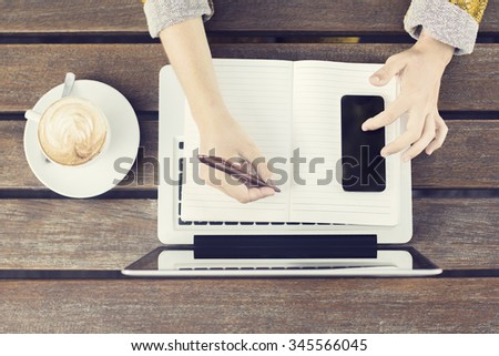Girl with laptop, blank diary, cell phone and coffee mug on wooden table - stock photo