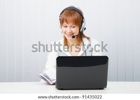 girl with laptop in headphones with a microphone. HotLine - stock photo