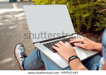 Girl with laptop in the park. Beautiful background - stock photo