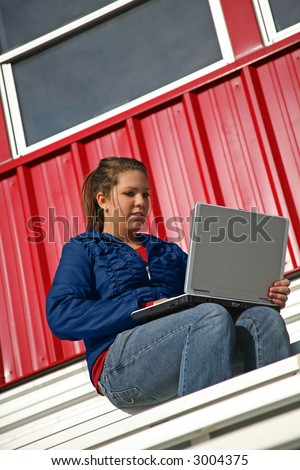 girl with laptop on the bleachers - stock photo