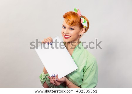 Girl with laptop, pc. Closeup red head beautiful young woman pretty smiling pinup girl green button shirt holding personal computer smiling looking at you camera, retro vintage 50's, 60's hairstyle - stock photo