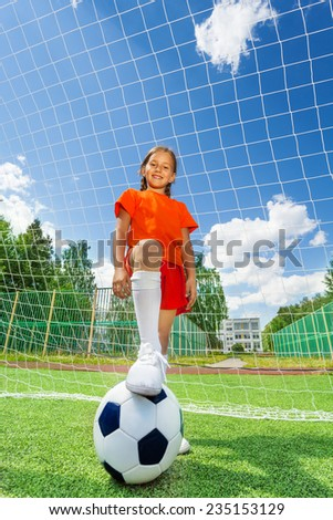 Girl with leg on football stands in front of white net of woodwork on sky background - stock photo