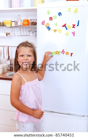 Girl with letter fridge magnets in the kitchen - stock photo