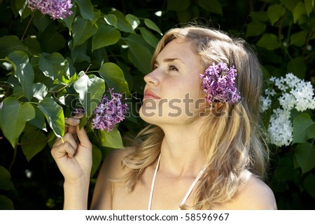 Girl with lilac in garden. - stock photo