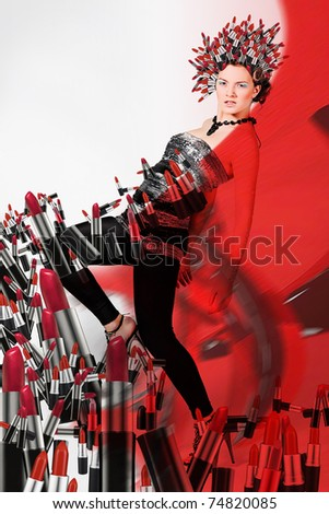 Girl with lipsticks around and on the head and red background