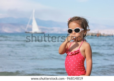 Girl with lollipop on the beach - stock photo