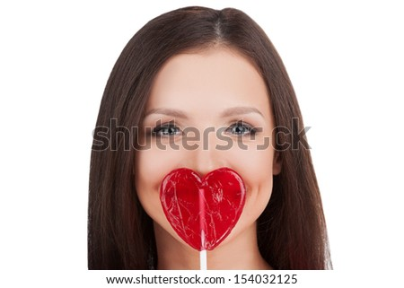 Girl with lollipop. Portrait of beautiful young woman holding heart shape lollipop in front of her lips while isolated on white - stock photo
