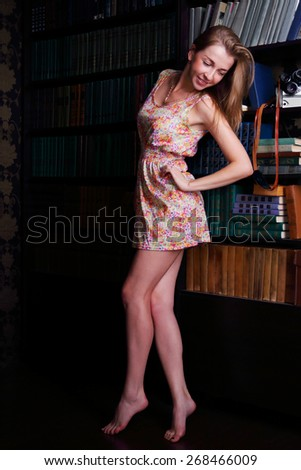 Girl with long blond hair in short dress standing next to shelves of books - stock photo