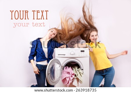Girl with long flowing hair sitting on the washing machine with the laundry for washing
