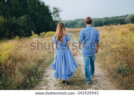 girl with long hair and a blue dress with polka dots, and the guy in the blue dress walk on the road in a field at sunset - stock photo